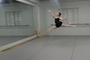 Salto realizado por la joven bailarina donde eleva sus piernas.